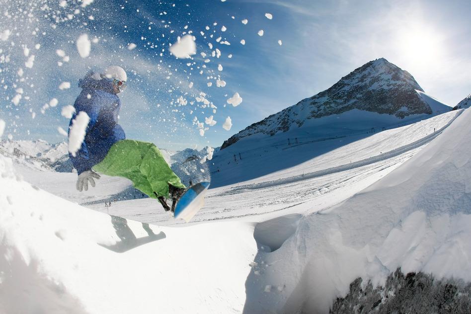en person står på snowboard på bjerg