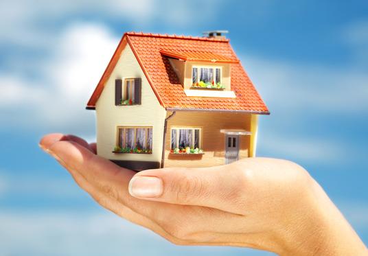 et lille hus holdes oppe af en menneskehånd