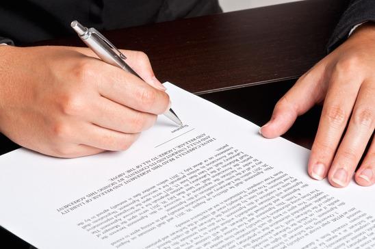 en kvinde er i gang med at underskrive et dokument