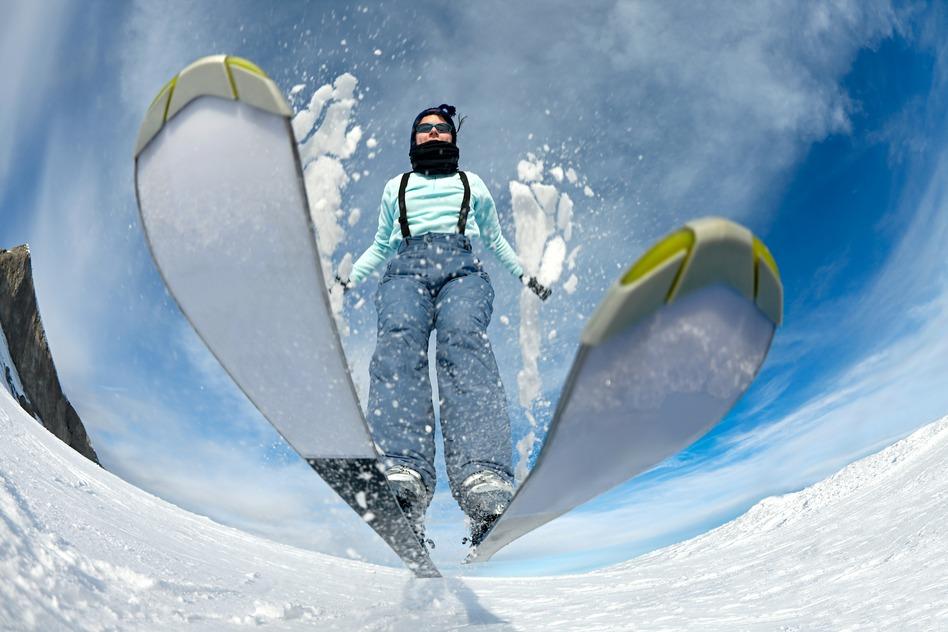 en mand med lyseblåt tøj står på ski på hvid sne