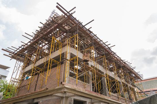 en bygning er ved at blive bygget med stålstær og hejs