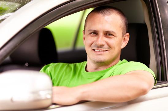 en ung mand i grøn trøje sidder i en bil og smiler